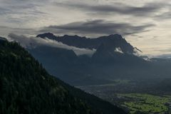 Highest mountain of germany with clouds rolling over it stock photography