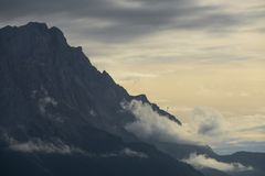 Highest mountain of germany with clouds rolling over it stock photo