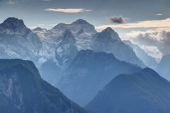 Snowy Triglav peak and misty Kot Valley, Julian Alps, Slovenia stock photo