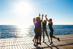 给highfive近的海的嬉戏女孩剪影在日出 图库摄影