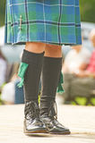 Highland dress detail. An image of socks and shoes of a Scottish Piper in formal dress also showing tartan kilt and sword shaped pin Stock Photography