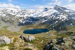 Highland lake between snow mountains area Royalty Free Stock Photos