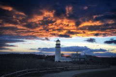 Highland Lighthouse Sunset cape cod. The Highland Lighthouse against a beautiful dramatic sunset in North Truro Massachusetts on the Cape Cod National Seashore stock image