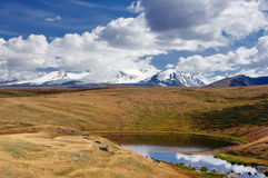 Highland little round lake on the background of high snow mountain peaks Royalty Free Stock Image