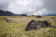 Highland pasture with stones against fog clouds Stock Image