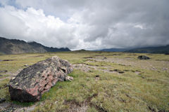 Highland pasture with stones against fog clouds Royalty Free Stock Photos