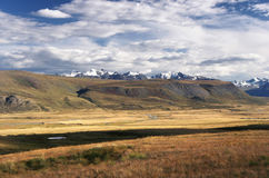 A highland river valley with yellow grass on a background of snow covered mountains and glaciers Stock Photo