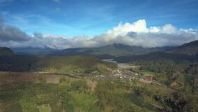 Highland Valley with Lake Village and Fields Flight View. Picturesque highland landscape aerial panorama green forestry hills large lake village and fields stock footage