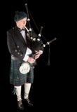 Highlander playing. Scottish highlander wearing kilt and playing bagpipes Royalty Free Stock Photography