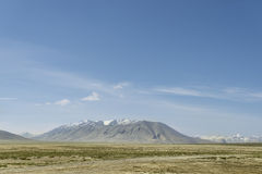 Highlands road among snowcapped summits Royalty Free Stock Photography
