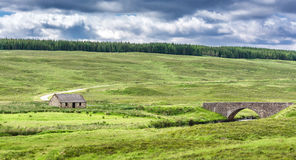 The Highlands of Scotland. Cabin and bridge surrounded by green hills royalty free stock photo