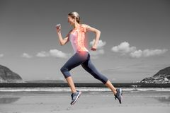 Highlighted back bones of jogging woman on beach Stock Photos