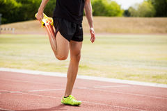 Highlighted bones of athlete man stretching on race track Royalty Free Stock Image