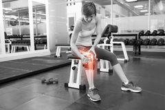 Highlighted bones of injured woman at gym. Digital composite of Highlighted bones of injured woman at gym royalty free stock photography