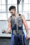 Highlighted bones of strong man lifting weights at gym royalty free stock photography