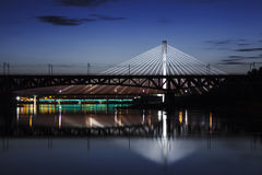Highlighted bridge at night and reflected in the water Stock Photo