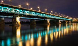 Highlighted bridge at night and reflected in the water. Royalty Free Stock Images