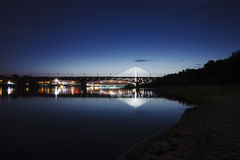 Highlighted bridge at night and reflected in the water Stock Photography