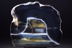 The highlighted Cut of black agate. On a dark background Stock Photos