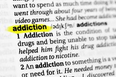 Highlighted English word `addiction` and its definition in the dictionary stock images