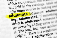 Highlighted English word adulterate and its definition in the dictionary.  Stock Image