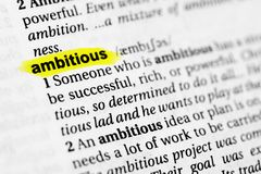 Highlighted English word `ambitious` and its definition in the dictionary.  Stock Image