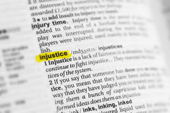 Highlighted English word & x22;injustice& x22; and its definition at the dictionary Stock Images