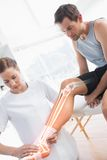 Highlighted knee of injured man at physiotherapist Stock Photos