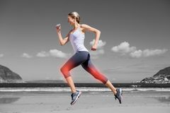 Highlighted leg of jogging woman on beach Stock Images