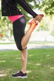 Highlighted leg of stretching woman Stock Photo