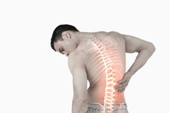 Highlighted spine of man with back pain. Digital composite of Highlighted spine of man with back pain Stock Photo
