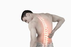 Highlighted spine of man with back pain. Digital composite of Highlighted spine of man with back pain Stock Photos