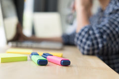 Highlighter on table with bcakground of student sitting in room Stock Photo