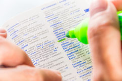 Highlighting the Ethic word on a dictionary. Close-up of a man hands using a florescent green marker to highlight the Ethic word on a dictionary royalty free stock photography