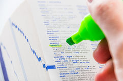 Highlighting the Search word on a dictionary. Close-up of a man hands using a florescent green marker to highlight the Search word on a dictionary stock photography