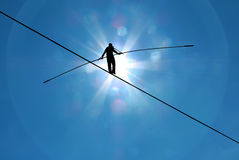 Highline walker in blue sky concept of risk taking and challenge. Tightrope walker balancing on the rope concept of risk taking and challenge Stock Photos