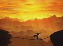 Highline walker silhouette in mountains at sunset . Stock Photography