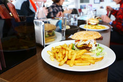 Highly caloric hamburger. Big burger and fries on the table of a fastfood restaurant Royalty Free Stock Photos