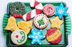 Decorated Christmas Cut Out Cookies on Green Glass Platter. Highly decorated and colorful Christmas cut out cookies that are homemade and set on a green glass Stock Photos