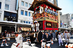 A highly decorated float along with its accompanying men in trad Stock Photo