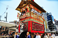 A highly decorated float along with its accompanying men in trad Royalty Free Stock Image