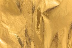Highly detailed texture of a rusty golden yellow shimmering thermal blanket background. royalty free stock image