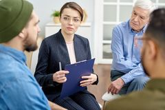 Group Therapy Session at Cozy Office. Highly professional psychologist in formalwear working with depressed patient while conducting group therapy session at royalty free stock photography