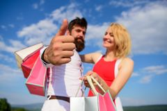 Highly recommend sale tips. Advice shop now. Couple with shopping bags cuddle blue sky background. Man with beard shows. Thumb up gesture. Couple in love stock image