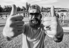Highly recommend top list events. Hipster visiting event picnic fest or festival. Man cheerful face shows thumb up. Man. Bearded in front of crowd riverside stock photo