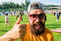 Highly recommend top list. Hipster visiting event picnic fest or festival. Man bearded in front of crowd riverside. Background. Man cheerful face shows thumb up royalty free stock images