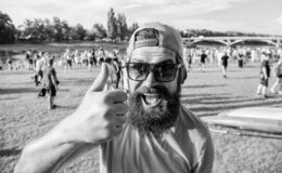 Highly recommend top list. Hipster visiting event picnic fest or festival. Man bearded in front of crowd riverside. Highly recommend top list. Man bearded in royalty free stock images