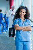 Highly successful medical student. Content afroamerican medical student with stethoscope in blue uniform standing on stairs Stock Photo