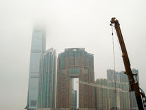 Highrise buildings- skyscraper and construction crane in foggy weather Royalty Free Stock Image