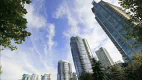Highrise Condominium Buildings in Downtown Vancouver BC Canada with Moving White Clouds and Blue Sky Time Lapse. 1920x1080 stock footage